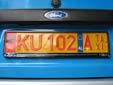 Taxi plate (old style) with a euroband sticker. KU = Kukës