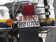 Traffic police motorcycle plate. 교통안전 = traffic safety<br>평양 = Pyongyang<br>(detailed view of the previous picture)